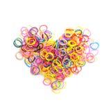 Kleine runde bunte Gummibänder im Herzen formen Stockfotos
