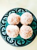 Kleine runde Donuts mit Kokosnuss auf Platte Stockfotos