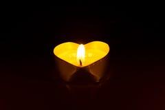 Kleine runde Kerze mit Herz-förmiger Tablette wird in der Dunkelheit beleuchtet Lizenzfreie Stockfotos