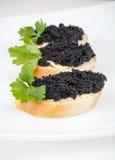 Kleine sandwiches met zwarte kaviaar op wit Stock Foto