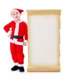 Kleine Santa Claus, die nahe großer Wunschliste steht Stockbilder