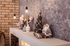 Kleine Santa Claus, die am oberen Teil des zeitgenössischen Kamins sitzt Lizenzfreie Stockfotos