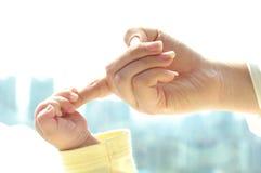 Kleine Schätzchenhand in einem erwachsenen Finger Lizenzfreies Stockfoto