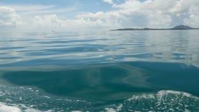 Kleine schäumende blaue Wellen nach einem Boot und einem ruhigen Ozean am bewölkten Tag Idyllisches tropisches waterscape Der Him stock video footage