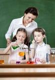 Kleine Schüler studieren chemische Flüssigkeiten Stockfoto