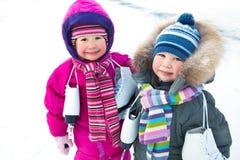 Kleine schaatsers in wintertijd stock afbeeldingen