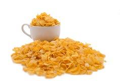 Kleine Schale Corn Flakes mit Stapel von Corn Flakes hinter weißem Ba Stockbilder