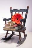 Kleine schommelstoel met boeken en bloem Royalty-vrije Stock Foto's