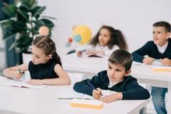 Kleine schoolkinderen die bij bureaus zitten en in oefenboeken schrijven royalty-vrije stock foto