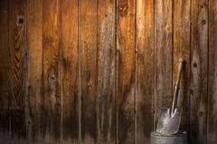 Kleine schop die tegen houten omheining leunen Stock Fotografie