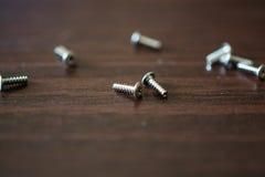 Kleine Schrauben am Holztisch Stockfotografie