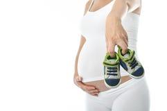 Kleine Schuhe der schwangeren Vertretung Stockfotografie
