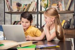 Kleine Schulkinder, die zusammen studieren und Laptop verwenden Lizenzfreies Stockfoto