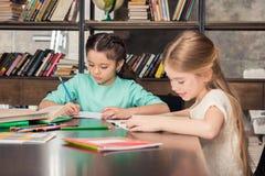 Kleine Schulmädchen, die bei Tisch sitzen und zusammen studieren Lizenzfreie Stockfotos