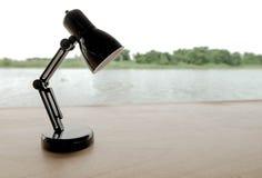 Kleine schwarze Lampe auf Holztisch mit Fluss und Wald als Hintergrund im zurückhaltenden Ton Lizenzfreies Stockbild