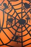 Kleine schwarze Spinnen auf Netz auf orange Hintergrund Stockfotografie