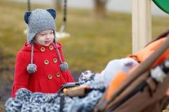 Kleine Schwester, die mit einem Baby in einem Spaziergänger spricht Stockfotografie