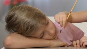 Kleine Schwestermalerei auf Gesicht des schlafenden Jungen, glückliche Kindheit, lustiger Streich stock footage