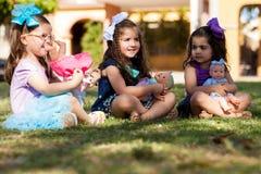 Kleine Schwestern, die mit Puppen spielen Lizenzfreie Stockfotografie