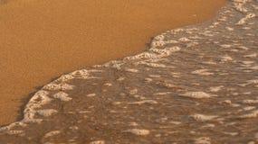 Kleine Seewelle über Sand, kleine Blasen des Wassers Lizenzfreie Stockbilder