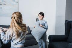 Kleine siblings die in pyjama's met hoofdkussens thuis vechten Stock Foto