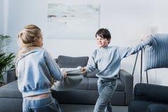 Kleine siblings die in pyjama's met hoofdkussens thuis vechten Stock Foto's