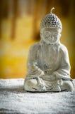 Kleine Skulptur von Buddha über weißen Kieseln Stockfoto