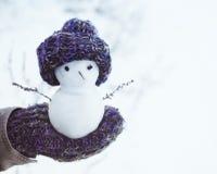Kleine sneeuwman in een gebreid GLB op een vuisthandschoen tegen de achtergrond van sneeuw in de winter Feestelijke achtergrond m Stock Foto's