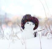 Kleine sneeuwman in een gebreid GLB op sneeuw in de winter Feestelijke achtergrond met een mooie sneeuwman Royalty-vrije Stock Afbeeldingen