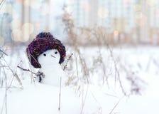 Kleine sneeuwman in een gebreid GLB op sneeuw in de winter Feestelijke achtergrond met een mooie sneeuwman Stock Foto's