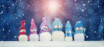 Kleine snowmans op zachte sneeuw op blauwe achtergrond stock afbeelding