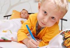 Kleine Sohnzeichnung in das Bett lizenzfreies stockfoto