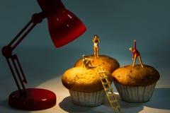 Kleine Spielwaren, die Badeanzug auf kleinen Kuchen tragen Lizenzfreie Stockbilder