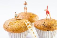 Kleine Spielwaren, die Badeanzug auf kleinen Kuchen tragen Stockfotos