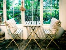 Kleine Stühle und Tabelle mit Gartenansicht durch Fenster Lizenzfreie Stockfotografie