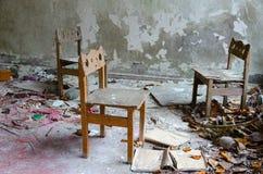 Kleine Stühle unter Schmutz und Rückstand in verlassenem Kindergarten, tote Stadt von Pripyat, Tschornobyl NPP-Ausschlusszone, Uk stockfotografie