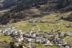 Kleine stad bij helling van de berg van de Alp stock afbeelding