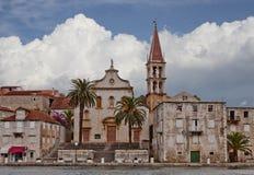 Kleine stad met kerk en palmenbomen bij het overzees Royalty-vrije Stock Afbeeldingen