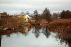 Kleine stad op de herfst van de rivierbank stock foto