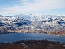 Kleine Stadt durch den See, der mit Schnee umgeben wurde, bedeckte Berge mit einer Kappe Stockbilder