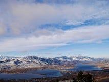 Kleine Stadt durch den See, der mit Schnee umgeben wurde, bedeckte Berge mit einer Kappe Lizenzfreie Stockfotos