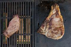 Kleine Steaks gegen großes Rindfleischsteak auf dem Grillkonzept lage klein wie das europäische amerikanische Lebensmittelessen lizenzfreies stockfoto