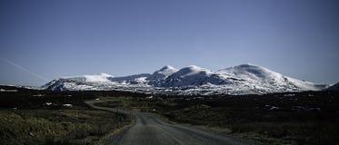Kleine Straße, die zu den schneebedeckten Hügeln vorangeht stockfoto