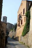 Kleine Straße unter alten Steinwänden, einem Haus und dem Turm des Schlosses in ArquàPetrarca Venetien Italien Stockbild
