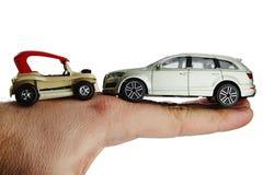 Kleine strandstuk speelgoed auto die met fouten zich op rug van volwassen mannelijke mensenhand tegen grote zilveren metaalsuv-au Royalty-vrije Stock Foto