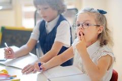Kleine Studenten, die mit Sorgfalt ihre Hausarbeit tun Lizenzfreie Stockbilder