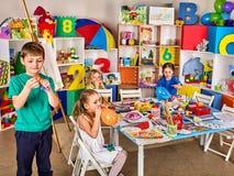 Kleine Studenten mit Lehrermalerei in der Kunstschulklasse Lizenzfreie Stockbilder