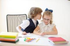 Kleine Studenten tun mit Sorgfalt eine Hausarbeit Lizenzfreie Stockbilder