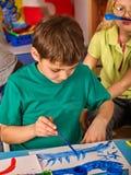 Kleine Studentenjungenmalerei in der Kunstschulklasse Lizenzfreie Stockbilder
