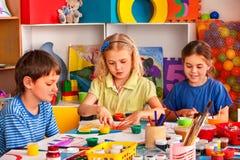 Kleine Studentenkinder, die in der Kunstschulklasse malen Stockbilder